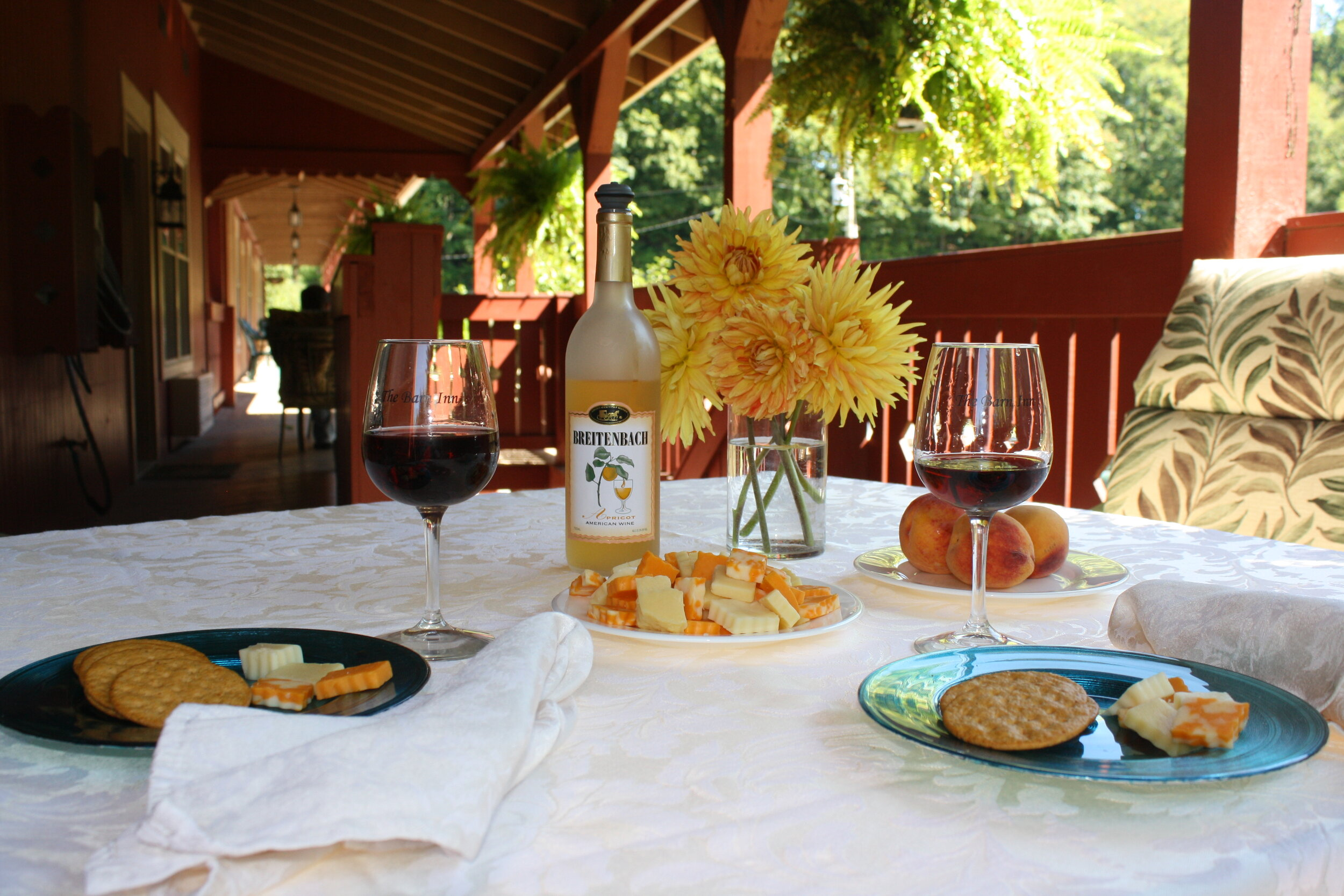 Wine and cheese on an outdoor deck with flowers